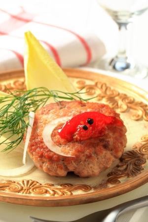 andijvie: Gebakken hamburger gegarneerd met andijvie bladeren Stockfoto