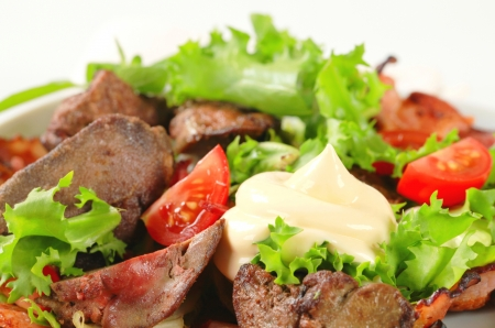 Pan fried chicken livers with salad greens and bacon strips photo