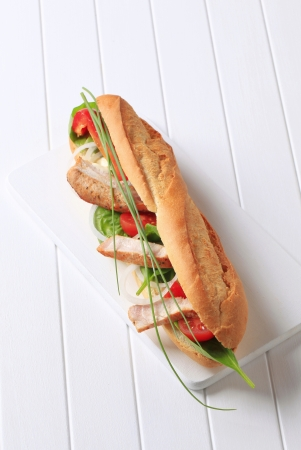 French bread filled with vegetables and chicken strips photo