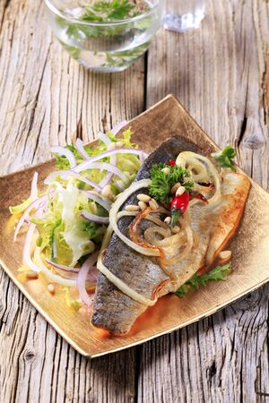 Pan fried trout fillet garnished with salad greens and onion photo