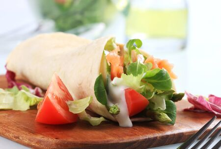 Tortilla filled with fresh vegetables and smoked salmon  photo