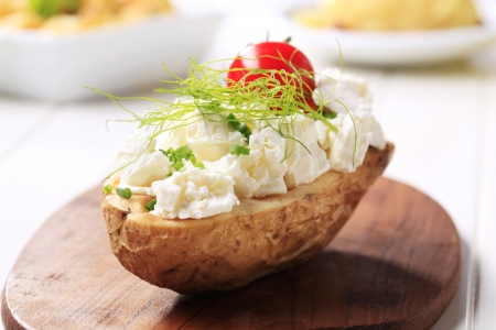 Baked potato topped with cheese photo