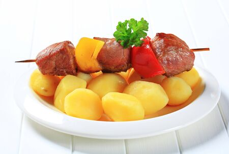 Chunks of grilled meat on skewer with potatoes photo