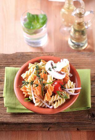 twists: Tri-color corkscrew pasta in a terracotta bowl