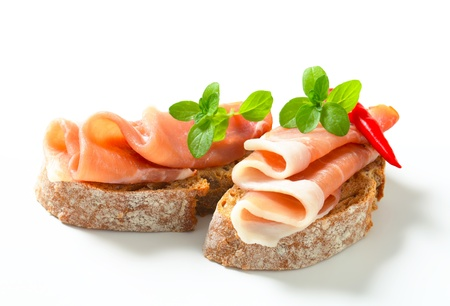 antipasto: Prosciutto open faced sandwiches garnished with red chili peppers
