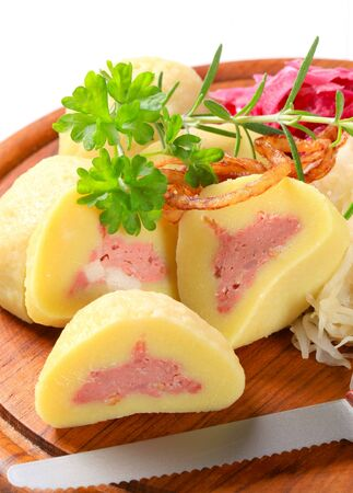 Meat stuffed potato dumplings with shredded cabbage on cutting board photo