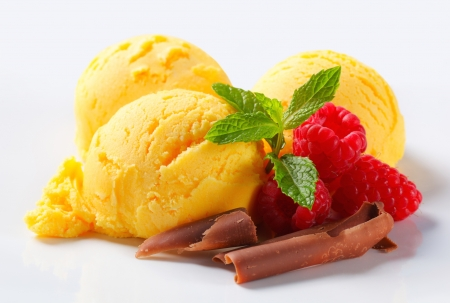 ice cream: Three scoops of yellow ice cream with raspberries and chocolate curls