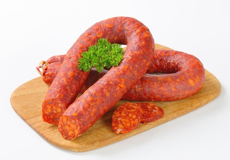 Spicy dry sausages on wooden cutting board Stock Photo