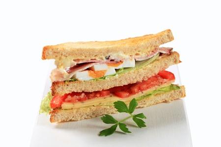 Deli sandwich with ham, cheese, egg and veggies photo