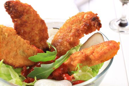 Crispy chicken tenders with tomato dipping sauce and lettuce