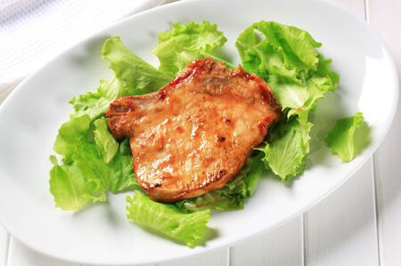 Glazed pork chop on lettuce leaves photo