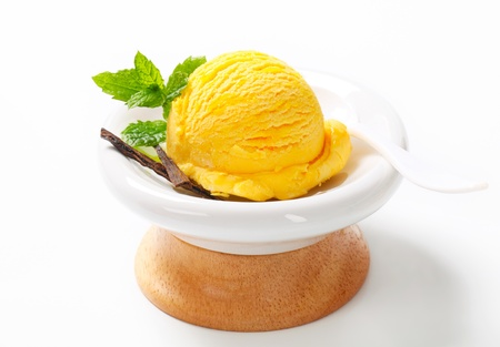 Scoop of yellow ice cream in a modern dessert dish photo