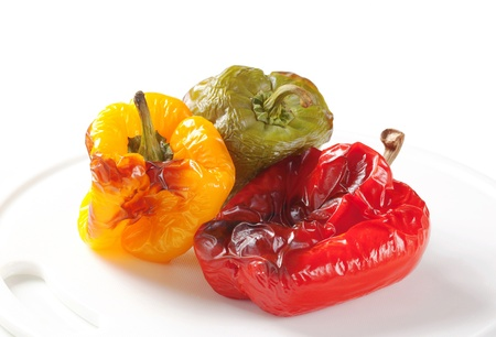 Three roasted bell peppers on a cutting board Stock Photo