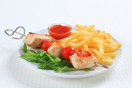 Chicken skewer with French fries and ketchup photo