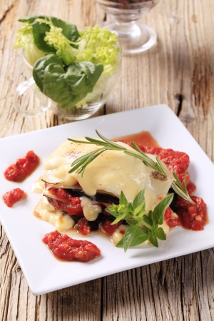Tomato and aubergine lasagna topped with cheese sauce photo