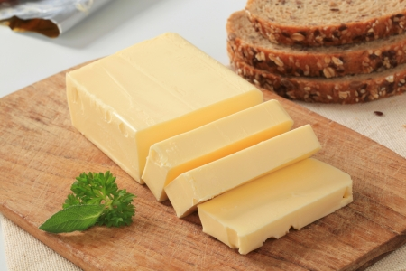 dairy product: Block of fresh butter and brown bread