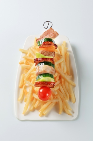 Pork and vegeable skewer with French fries Stock Photo