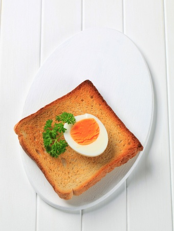Slice of toasted bread and boiled egg photo