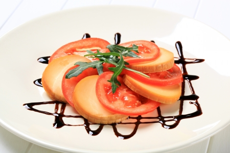 drizzle: Sliced tomato and smoked cheese garnished with balsamic vinegar