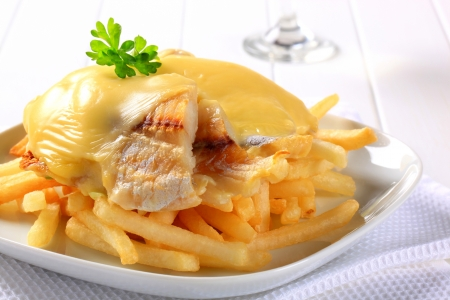Cheese topped fish fillets served with French fries photo