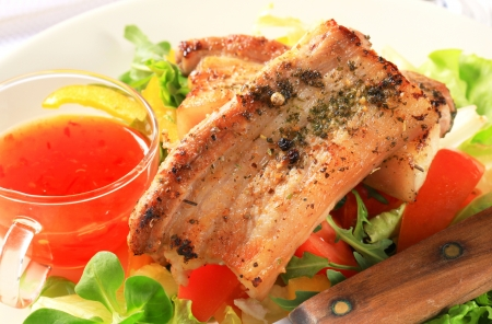 Herb rubbed pork belly slices with salad and hot sauce photo