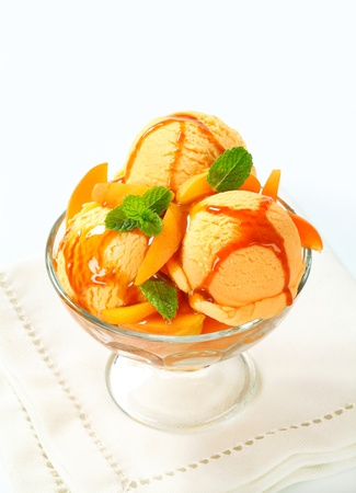 Ice cream with fresh apricot and caramel sauce photo