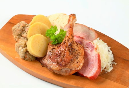 Roast duck and pork meat with three kinds of dumpling and white cabbage photo