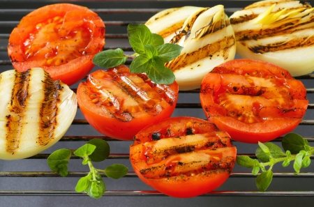 Grilled tomatoes and onions on barbecue grid Stock Photo