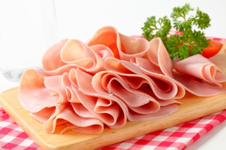 thinly: Thinly sliced ham on cutting board