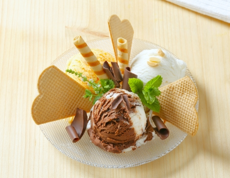 Scoops of ice cream garnished with wafers and chocolate curls photo