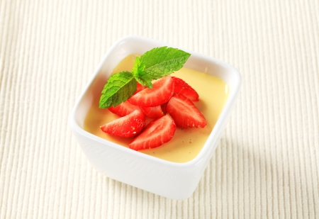 Small dish of vanilla pudding topped with strawberries photo