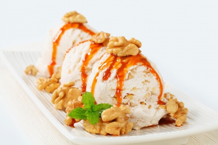 Scoops of walnut ice cream with caramel sauce photo