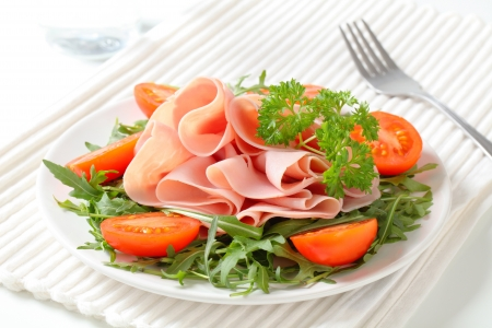 roquette: Sliced ham on nest of rocket salad Stock Photo