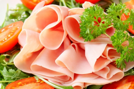 sliced: Sliced ham on nest of rocket salad Stock Photo