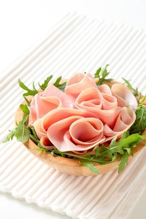 Sliced ham on nest of rocket salad Stock Photo