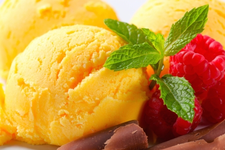 Scoops of yellow ice cream with raspberries and chocolate curls