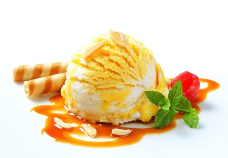 Scoop of yellow white ice cream with caramel sauce photo