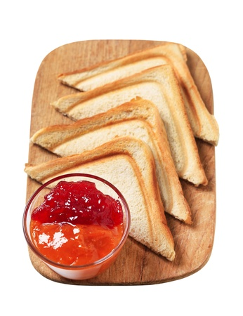 Slices of toasted bread and bowl of preserves photo