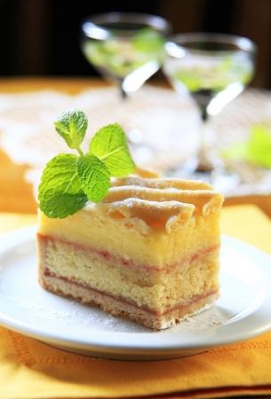 rum cake: Fetta di pan di spagna imbevuto di rum con crema alla vaniglia Archivio Fotografico
