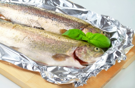 Two fresh trout on tin foil photo