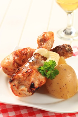 Spicy chicken drumsticks and new potatoes - closeup photo