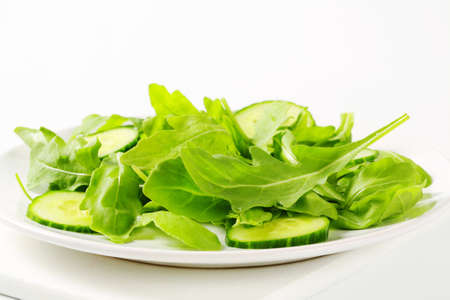 Fresh rocket salad with sliced cucumber photo