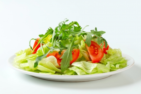 side salad: Ice lettuce leaves with tomato wedges and arugula