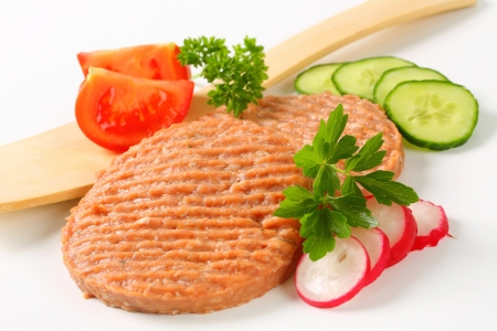 Studio shot of raw burger patties and sliced vegetables photo