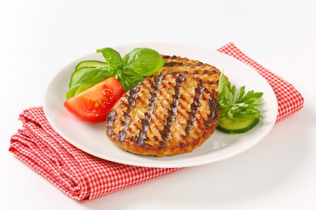 Grilled patties garnished with sliced cucumber and tomato Standard-Bild