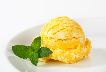 Scoop of pineapple or mango ice cream photo