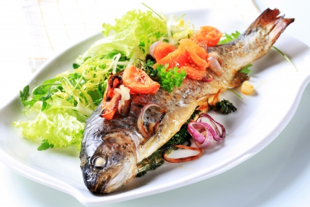Herb-stuffed trout with tomatoes and green salad