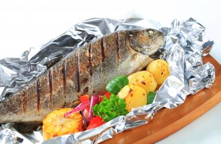 pescado frito: Trucha a la plancha sobre papel de aluminio Foto de archivo