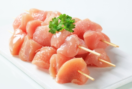 Raw chicken skewers on cutting board Standard-Bild