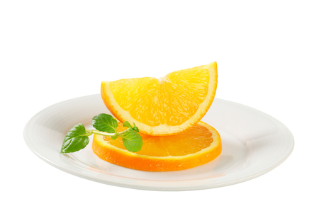 Slices of fresh orange on plate photo